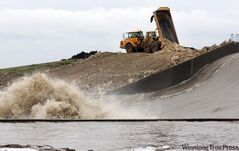 Heavy-equipment operators shore up the walls of the Portage Diversion on Tuesday. The diversion is full to capacity running towards Lake Manitoba.