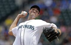 Seattle Mariners starting pitcher Chris Young throws to the Oakland Athletics in the first inning of a baseball game Sunday, July 13, 2014, in Seattle. (AP Photo/Elaine Thompson)
