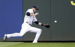 Seattle Mariners right fielder Michael Saunders stumbles as he chases a triple hit by Kansas City Royals' Mike Moustakas in the third inning of a baseball game on Saturday, May 10, 2014, in Seattle. Saunders later left the game. (AP Photo/Elaine Thompson)