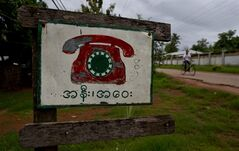 In this June 14, 2013 photo, a roadside sign advertises a phone call facility in Hmawbi, on the outskirts of Yangon, Myanmar. Foreign companies will tap into one of the world's final telecom frontiers Thursday, June 27, 2013, when Myanmar hands out licenses to operate two new mobile phone networks — part of efforts by the long-isolated nation to use technology to spur economic development. The sign reads