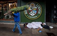 A man carries a Christmas tree to as a homeless man sleeps on the sidewalk in Vancouver, B.C., on December 10, 2012. THE CANADIAN PRESS/Darryl Dyck