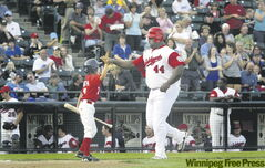 Goldeyes DH Juan Diaz gives the bat boy a high-five after socking his 23rd home run of the season during Thursday night's Northern League game against Joliet.