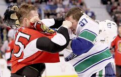 Ottawa Senators' Chris Neil connects against Rick Rypien of the Vancouver Canucks during an NHL game in February 2010.