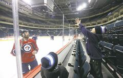 Winnipeg Jets defenceman Zach Bogosian tosses pucks to fans Zaden Hnidy, 6 and his brother, Colby, 8, during practice at  the MTS Centre Monday. The Jets head to Buffalo to take on the Sabres tonight.