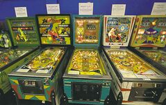 Older pinball machines line a wall of the Seattle Pinball Museum.