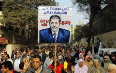 Supporters of Egypt's ousted President Mohammed Morsi hold his poster as they raise their hands with four fingers which has become a symbol of the Rabaah al-Adawiya mosque, where Morsi supporters had held a sit-in for weeks that was violently dispersed in August, during a protest in Cairo, Egypt, Friday, Dec. 20, 2013. Arabic reads,