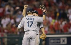 Seattle Mariners' Kyle Seager, facing camera, and Justin Smoak celebrate the team's 3-2 win against the Los Angeles Angels in 12 innings in a baseball game Saturday, July 19, 2014, in Anaheim, Calif. (AP Photo/Jae C. Hong)