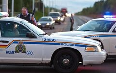 RCMP officers use their vehicle to create a keep a perimeter in Moncton, N.B.on Wednesday June 4, 2014. The RCMP in New Brunswick says an undisclosed number of people have been shot and a manhunt is underway in the north end of Moncton for a man armed with guns. THE CANADIAN PRESS/Marc Grandmaison