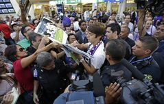 Brazilian soccer star Kaka, center, signs autographs as he is surrounded by fans at Orlando International Airport, Monday, June 30, 2014, in Orlando, Fla. Kaka is the first designated player to sign with the Orlando City Soccer Club that will begin play in Major League Soccer in 2015. (AP Photo/John Raoux)