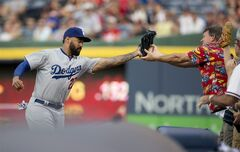 Los Angeles Dodgers left fielder Matt Kemp (27) battles a fan for a foul ball by Atlanta Braves' Mike Minor in the second inning of a baseball game Tuesday, Aug. 12, 2014, in Atlanta. (AP Photo/John Bazemore)