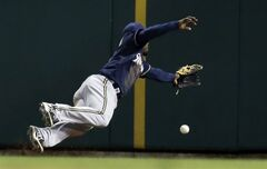 Milwaukee Brewers left fielder Elian Herrera dives but cannot reach a ball hit for an RBI triple by St. Louis Cardinals' Allen Craig during the seventh inning of a baseball game Tuesday, April 29, 2014, in St. Louis. (AP Photo/Jeff Roberson)