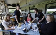 In this June 6, 2014 photo, servers Lindsey Hayden, second from left, and Emma Franz serve lunch to patrons at Coppertop restaurant in Valley City, Ohio. A Federal Reserve survey released Wednesday, July 16, 2014 indicates the economy kept expanding in all regions of the country in June and early July, helped by strength in consumer spending. (AP Photo/Mark Duncan)