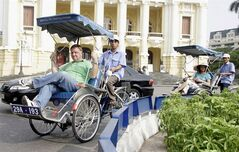 Tourists ride in their cyclos past the Opera House in Hanoi, Vietnam, Oct. 20, 2006. THE CANADIAN PRESS/HO, Tran Van Minh