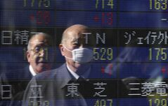 People are reflected on the electronic board of a securities firm in Tokyo, Jan. 16, 2014. THE CANADIAN PRESS/AP, Koji Sasahara