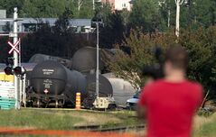 A resident takes pictures of the crash site after a train derailed Saturday causing explosions of railway cars carrying crude oil Tuesday, July 9, 2013 in Lac-Megantic, Que. THE CANADIAN PRESS/Paul Chiasson