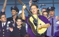 Paul McCartney is surrounded by firefighters and police personnel at the end of the Concert for New York in 2001.