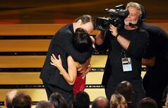 """Bryan Cranston, left, kisses Julia Louis-Dreyfus as she accepts the award for outstanding lead actress in a comedy series for her work on """"Veep"""" at the 66th Annual Primetime Emmy Awards at the Nokia Theatre L.A. Live on Monday, Aug. 25, 2014, in Los Angeles. (Photo by Chris Pizzello/Invision/AP)"""