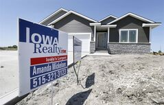 A sign sits in front of a new home for sale in West Des Moines, Iowa on May 21, 2014 photo. THE CANADIAN PRESS/AP, Charlie Neibergall