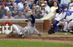 Atlanta Braves' Freddie Freeman, left, scores on a three-run double hit by Justin Upton as Chicago Cubs catcher Welington Castillo tries to catch the ball during the fourth inning of a baseball game in Chicago, Saturday, July 12, 2014. (AP Photo/Nam Y. Huh)