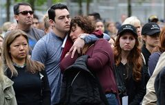 Two people embrace while gathered on the plaza of the National September 11 Memorial to watch the telecast of the dedication ceremony at the National September 11 Memorial Museum in New York on Thursday, May 15, 2014. (AP Photo/Justin Lane, Pool)