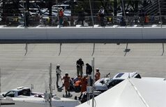 Workers and officials repair the track surface during the NASCAR Sprint Cup series auto race, Sunday, June 1, 2014, at Dover International Speedway in Dover, Del. (AP Photo/Nick Wass)