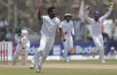 Sri Lankan bowler Dilruwan Perera , center, celebrates taking the wicket of South African batsman Alviro Petersen, left, during the fourth day of the first test cricket mach between them in Galle, Sri Lanka, Saturday, July 19, 2014. (AP Photo/Eranga Jayawardena)