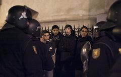 Demonstrators are held by riot police officers following a protest in Madrid, Spain, Sunday, Feb. 24, 2013. Tens of thousands of people marched on Spain's parliament on Saturday to protest austerity measures, a demonstration that came on the 32nd anniversary of a failed attempt by the armed forces to overthrow the government. Protest groups joined forces under the slogan
