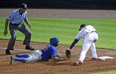 New York Mets' Eric Young Jr. (22) is tagged out by Atlanta Braves first baseman Freddie Freeman (5) while trying to get back to first base after being caught in a rundown in the fifth inning of a baseball game in Atlanta, Wednesday, July 2, 2014. Atlanta won 3-1. (AP Photo/John Bazemore)