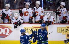 Members of the Calgary Flames look on as Vancouver Canucks left wing Chris Higgins (20) celebrates his game winning shoot out goal with teammate Daniel Sedin following NHL action against the Calgary Flames in Vancouver, B.C. Saturday, Jan. 18, 2014. THE CANADIAN PRESS/Jonathan Hayward