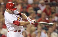 St. Louis Cardinals' Matt Holliday connects for an RBI single in the third inning of a baseball game against the Philadelphia Phillies, Friday, June 20, 2014, in St. Louis. (AP Photo/Tom Gannam)