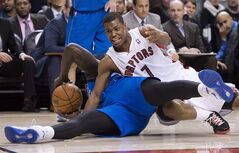 Toronto Raptors guard Kyle Lowry, right, battles for the ball against Dallas Mavericks forward DeJuan Blair, left, during first half NBA basketball action in Toronto on Wednesday, January 22, 2014. THE CANADIAN PRESS/Nathan Denette