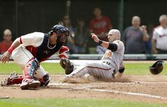 Baltimore Orioles' Steve Pearce, right, slides into home plate as Cleveland Indians catcher Yan Gomes is late on the tag in the sixth inning of a baseball game, Sunday, Aug. 17, 2014, in Cleveland. Pearce scored on a single by J.J. Hardy. (AP Photo/Tony Dejak)