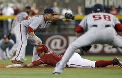Arizona Diamondbacks' Gerardo Parra (8) is forced out at second base by Washington Nationals' Ian Desmond, left, on a fielder's choice as Nationals pitcher Doug Fister (58) looks on during the first inning of a baseball game on Wednesday, May 14, 2014, in Phoenix. (AP Photo)