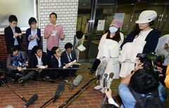 Rina Kawaei, second right, and Anna Iriyama, right, two members of Japan's hugely popular female pop group AKB48, speak to the media as they leave a hospital, wearing hats and covering their hands with towels, in Morioka, northern Japan, Monday, May 26, 2014, after being treated for hand and head injuries they suffered from an attack by a saw-wielding man during a fan meeting on Sunday. The group canceled fan events Monday after the attack on the two and a male staffer, who tried to stop the assault, shocking the nation and raising questions over security. (AP Photo/Kyodo News) JAPAN OUT, MANDATORY CREDIT