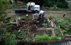 A Canadian Pacific Rail police officer, right, stands by as workers remove community gardens from a stretch of abandoned CP Rail line in Vancouver, B.C., on Thursday August 14, 2014. The once-abandoned 11-kilometre-long Arbutus Corridor has been used by residents for many years as a greenway where community gardens were erected. The removal of the gardens is the culmination of a growing dispute between the rail company and the City of Vancouver over the value of the land. THE CANADIAN PRESS/Darryl Dyck