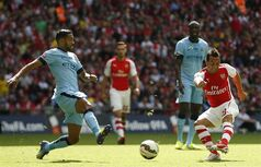 Arsenal's Santi Carzola, right, shoots and scores the opening goal past Manchester City's Gael Clichy during the English FA Community Shield soccer match at Wembley Stadium, London Sunday, Aug. 10, 2014. (AP Photo/Alastair Grant)