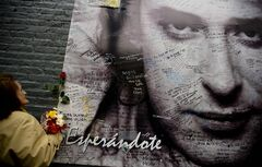 A woman places flowers on a poster of Argentine musician Gustavo Cerati that reads in Spanish: