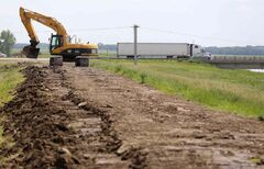 Construction crews work to bulk up the east side of the Portage Diversion near Highway 1, Saturday, July 5.