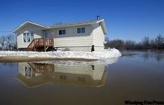 A house is protected by a sandbag dike on the Peguis First Nation in April 2011.