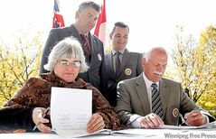 MPs James Bezan (left) and Rod Bruinooge watch as Vic Toews  and Christine Melnick sign agreement during ceremony at The Forks Monday.
