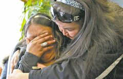 Tracy Okemow's sister Corina Okemow (left) is consoled by friend Celine Samuel as she weeps at a press conference Thursday.