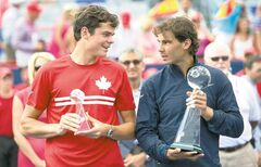 Canada's Milos Raonic (small trophy) chats with winner Rafael Nadal during the prize presentation Sunday in Montreal.