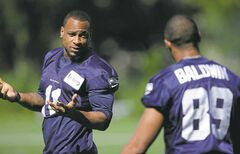 Seattle Seahawks wide receivers Percy Harvin, left, and Doug Baldwin, right, talk at the start of NFL football training camp, Thursday, July 31, 2014, in Renton, Wash. Harvin and Baldwin did not take part in drills on Thursday. (AP Photo/Ted S. Warren)