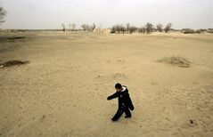 In this March 17, 2007 photo, a child walks on the sand dune in Waixi, Gansu province, China, where over-farming has drawn down the water table so low that desert is overtaking farmland. The United Nations said Friday that it is