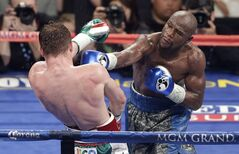 Floyd Mayweather Jr. throws a punch against Canelo Alvarez during a 152-pound title fight, Saturday, Sept. 14, 2013, in Las Vegas. (AP Photo/Isaac Brekken)