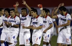 Paraguay's Nacional players celebrate after leveling the score in the last minute against Argentina's San Lorenzo at the end of the first leg of the Copa Libertadores soccer final in Asuncion, Paraguay, Wednesday, Aug. 6, 2014. The game ended in a 1-1 tie. (AP Photo/Jorge Saenz)