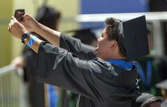 A UC Irvine student takes a selfie with his cell phone while waiting for President Barack Obama to arrive for the commencement ceremony Saturday, June 14, 2014, at Angel Stadium of Anaheim. (AP Photo/The Orange County Register,Bruce Chambers)