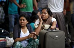 Women from India's northeastern states wait with their baggage to board trains home at a station in Bangalore, India, Thursday, Aug. 16, 2012. Thousands of Indians from the northeast are fleeing the southern city of Bangalore, spurred by rumors they would be attacked in retaliation for communal violence in their home state of Assam. (AP Photo/Aijaz Rahi)