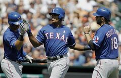 Texas Rangers' Leonys Martin, left, congratulates Adrian Beltre and Mitch Moreland (18) after they scored on a triple by Alex Rios during the fifth inning of a baseball game against the Detroit Tigers, Sunday, May 25, 2014, in Detroit. (AP Photo/Duane Burleson)