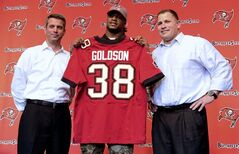 Tampa Bay Buccaneers general manager Matt Dominik, left, and coach Greg Shiano, right, pose with the newest Buccaneer Dashon Goldson during an NFL football news conference on Wednesday, March 13, 2013 in Tampa, Fla. Free agent safety Dashon Goldson signed a $41.25 million, five-year contract with the Tampa Bay Buccaneers on Wednesday. (AP Photo/The Tampa Tribune, Chris Urso) ST. PETERSBURG OUT; LAKELAND OUT; BRADENTON OUT; MAGS OUT; LOCAL TV OUT; WTSP CH 10 OUT; WFTS CH 28 OUT; WTVT CH 13 OUT; BAYNEWS 9 OUT